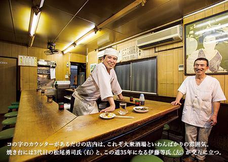 コの字のカウンターがあるだけの店内は、これぞ大衆酒場といわんばかりの雰囲気。焼き台には3代目の松尾勇司氏〈右〉と、この道35年になる伊藤等氏〈左〉が交互に立つ。